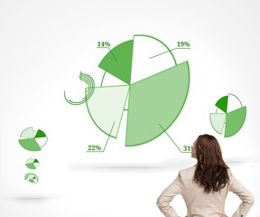 Businesswoman standing back to camera watching green diagrams