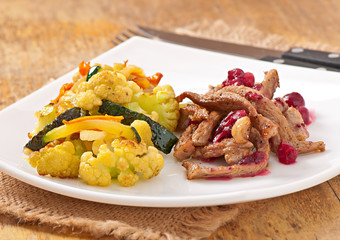 Beef stroganoff with cranberry sauce and grilled vegetables