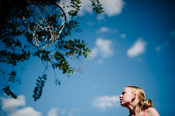 Yong blond girl looks up at basketball goal.