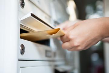 Woman putting envelope in mailbox Fototapete