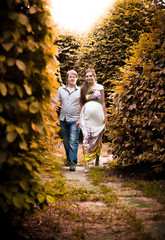 Pregnant woman and her husband walking in autumn park