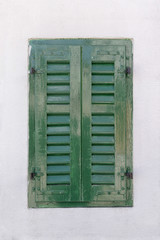 Window with green shutters in a white wall