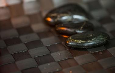 Black zen stones with water droplets