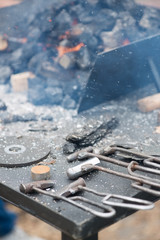 Old-fashioned blacksmith's instruments near forge fire