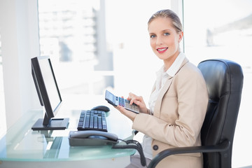 Side view of smiling blonde businesswoman using calculator