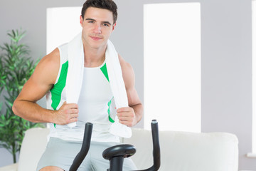 Smiling handsome man training on exercise bike