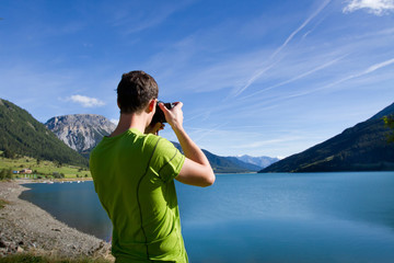 nature photographer near lake in mountains