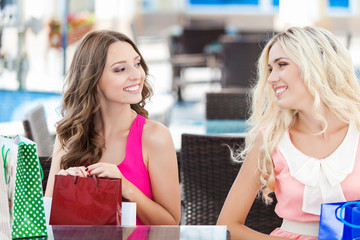 young women friends in cafe on terrace after the shopping