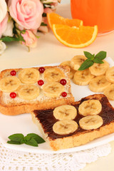 Delicious toast with bananas on plate close-up
