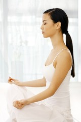 Side view of woman practicing yoga