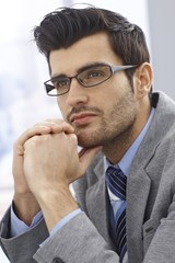 Portrait of handsome daydreaming businessman