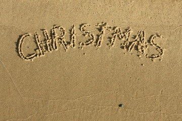 The word Christmas written on sand