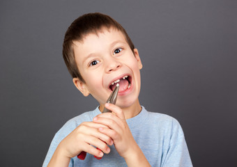 boy holds a lost tooth in the pliers