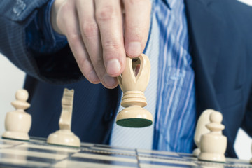 Business man moving chess figure with team behind