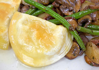 A close view of a pierogies meal with vegetables