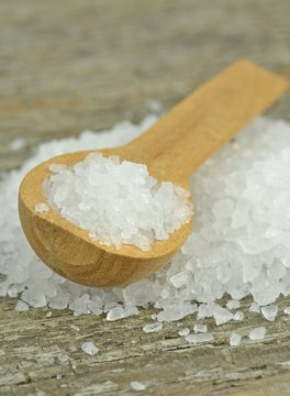 Natural sea salt crystals with wooden spoon on rustic table