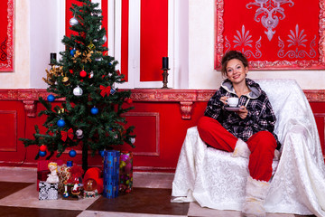 Girl in worm clothes inside a red vintage room with christmas de
