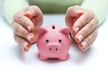 protect your savings - with hands and piggy bank