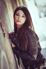 Beautiful japanese woman in urban background wearing leather jac
