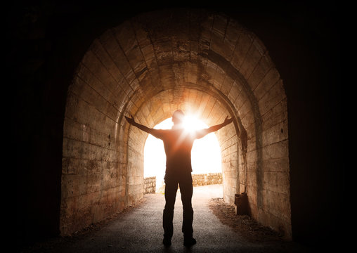 Man stands inside of old dark tunnel