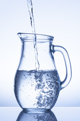 Flowing water in a jug on blue background