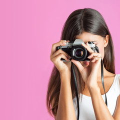 Woman with camera close up against pink background.