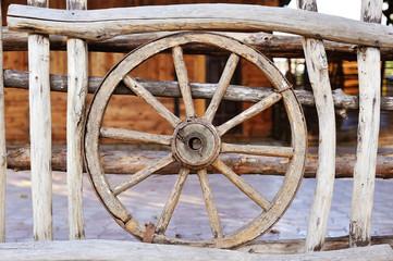 old wood coach wheel around barn