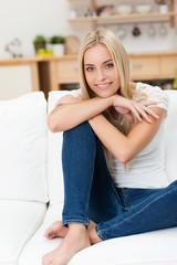 lächelnde junge frau sitzt entspannt auf dem sofa