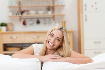 glückliche junge frau lehnt sich auf sofa