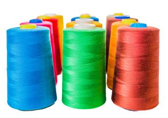 Colored fine thread bobbins on white