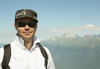 Man on background of Caucasus mountain range in Krasnaya Polyana