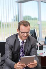 lächelnder mann im büro liest am tablet