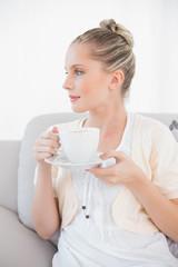 Pensive fresh model holding coffee sitting on sofa