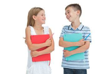 Smiling brother and sister holding their exercise books