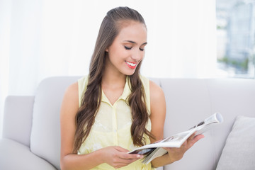 Smiling pretty brunette reading magazine