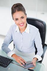 Smiling brunette businesswoman using calculator
