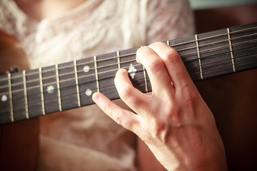 Clos eup on young woman's hand playing guitar
