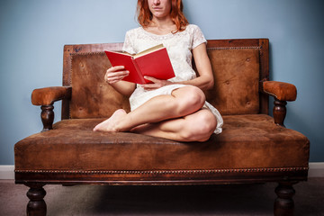 Young woman in summer dress is sitting on old sofa and reading