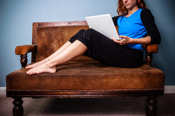 Young woman sitting on a sofa using her laptop