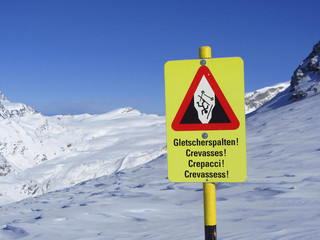"Warning sign ""Beware of Crevasses"" next to a ski slope"