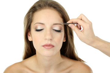 Young woman having eye-brows plucked isolated on white