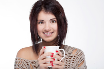 Portrait of a smiling girl holding a cup near the face