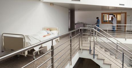 Patient lying in bed in quiet corridor