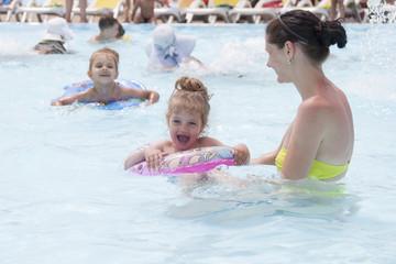 Мама и две дочери купаются в бассейне