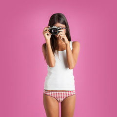Sensual girl portrait with camera against colorful pink backgrou