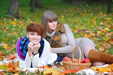 Young girls in the autumn park sitting on the grass