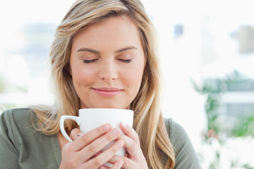 Woman with mug raised to near her mouth, eyes closed and smiling