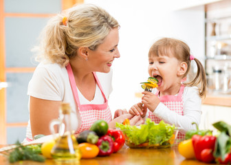 Wall Mural - mother feeding kid daughter vegetables in kitchen