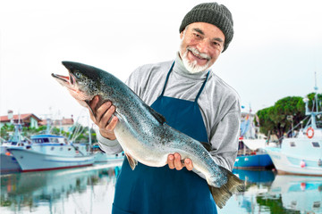 Fisherman holding a big atlantic salmon fish