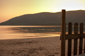 little fence on the beach with the sea at sunset
